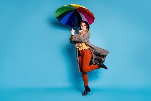Portret całego ciała ładnej podróżniczki, podnoszącej się, trzymaj kolorowe parasolowe ręce dmuchane powietrze nosić na co dzień długi szary płaszcz sweter pomarańczowe spodnie kapelusz buty.