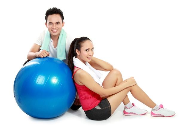 Portret całego ciała sportowy para z piłką pilates na białym tle