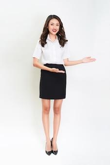 Portret całego ciała szczęśliwej uśmiechniętej młodej pięknej kobiety biznesu pokazującej coś lub copyspase