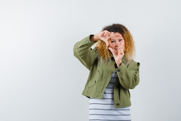 Portret całkiem blond kobieta robi gest ramy w zielonej kurtce i patrząc pewnie z przodu