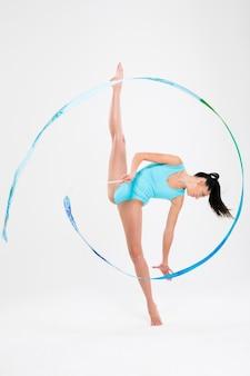 Portret całkiem elastyczna gimnastyczka kobieta na białym tle na białej ścianie