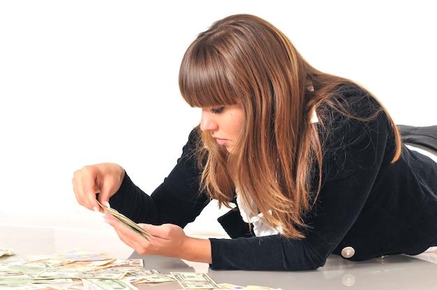 Portret całkiem kaukaski biała brunetka kobieta leżąca w pobliżu banknotów euro i dolarowych