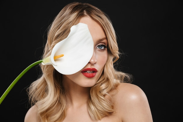Portret całkiem młoda blond kobieta z jasny makijaż czerwone usta pozowanie na białym tle gospodarstwa biały kwiat.