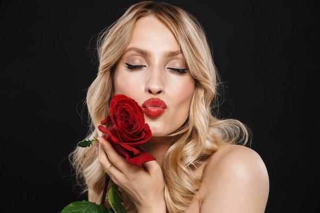 Portret całkiem młoda blond kobieta z jasny makijaż czerwone usta pozowanie na białym tle gospodarstwa kwiat róży dmuchanie buziakami.