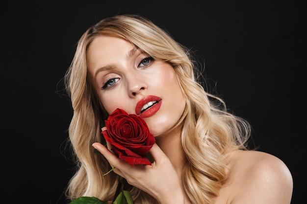 Portret całkiem młoda blond kobieta z jasny makijaż czerwone usta pozowanie na białym tle gospodarstwa kwiat róży.