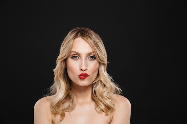 Portret całkiem młoda blond kobieta z jasny makijaż czerwone usta pozowanie na białym tle gryźć jej wargę.