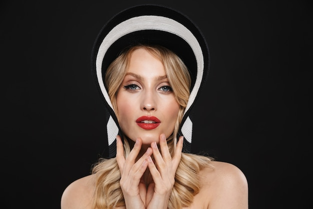 Portret całkiem młoda blond kobieta z jasny makijaż czerwone usta pozowanie na białym tle sobie kapelusz.