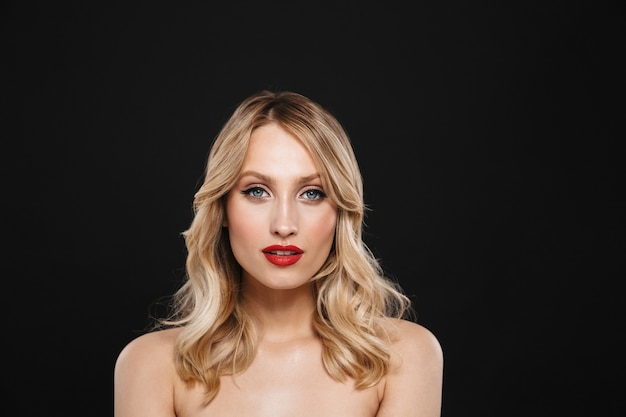 Portret całkiem młoda blond kobieta z jasny makijaż czerwone usta pozowanie na białym tle.