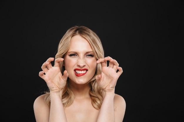 Portret całkiem młoda blondynka flirtuje warczenie kobiety z jasny makijaż czerwone usta pozowanie na białym tle.