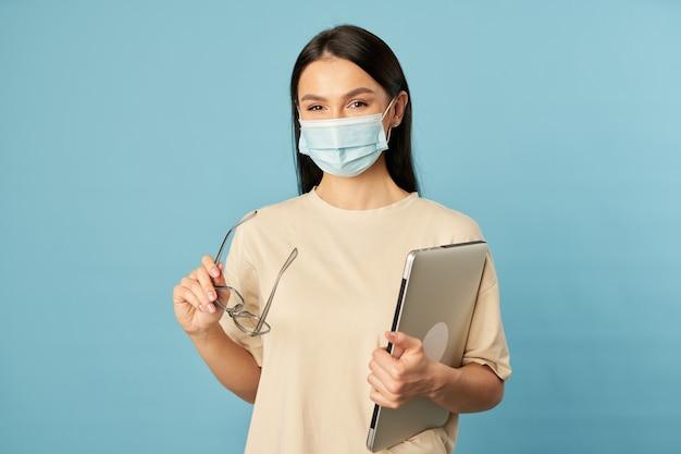Portret całkiem młoda dama za pomocą laptopa trzymając okulary i pozowanie w studio, na białym tle na niebieskim tle. skopiuj miejsce. kwarantanna, koncepcja epidemii