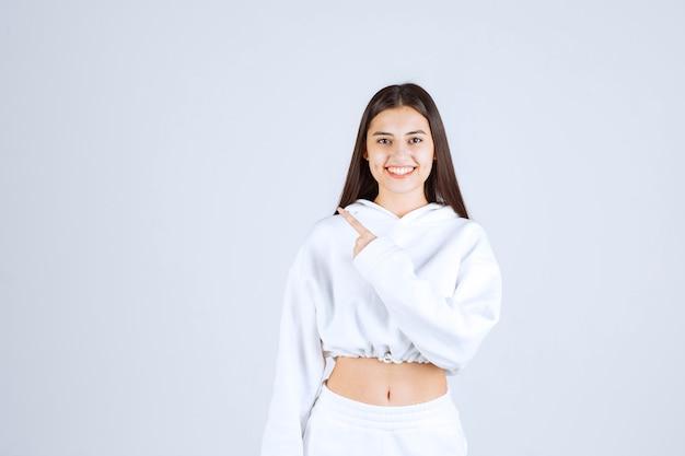Portret całkiem młoda dziewczyna modelu wskazując palcem wskazującym.