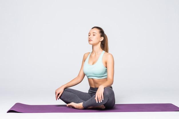Portret całkiem młoda kobieta robi medytację ćwiczenia jogi na macie na białym tle