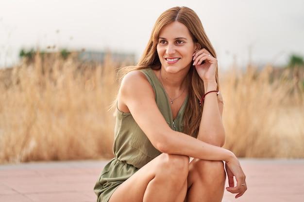 Portret całkiem młoda kobieta siedzi na chodniku na ulicy z ładnym nieostrym tłem.