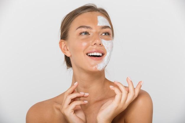 Portret całkiem młoda kobieta topless na białym tle, patrząc z pół twarzy zakrytej białą maską