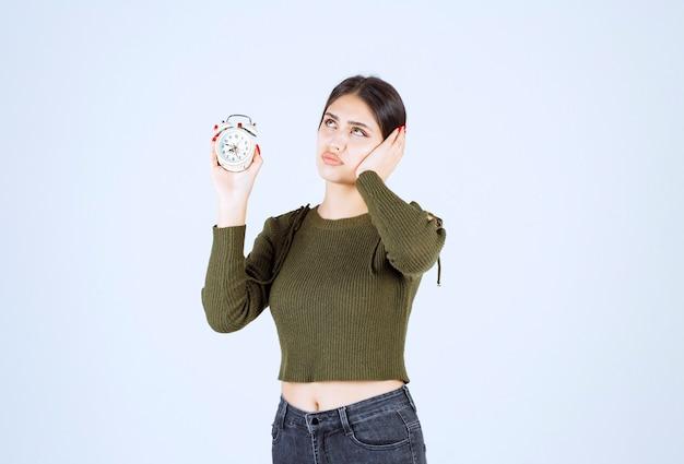 Portret całkiem młoda kobieta trzyma budzik z szalonym wyrazem.