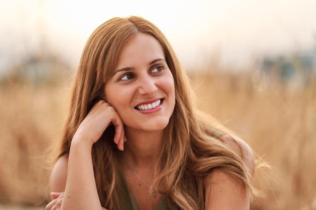 Portret całkiem młoda kobieta uśmiecha się z ładnym nieostrym tle.