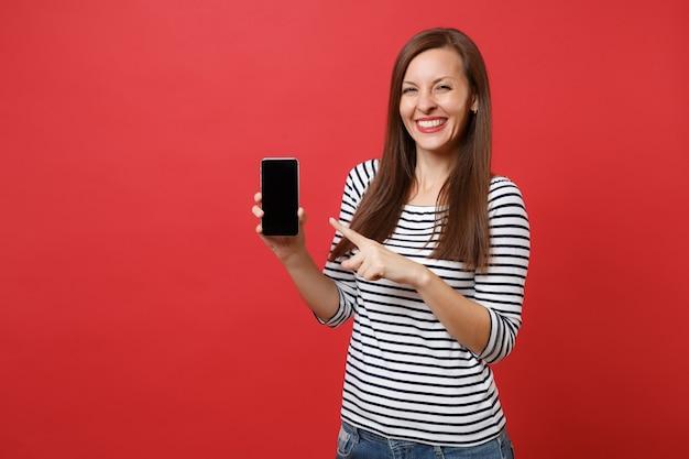 Portret całkiem młoda kobieta wskazując palcem wskazującym na telefon komórkowy z pustym czarnym pustym ekranie na białym tle na jasnym czerwonym tle. ludzie szczere emocje, koncepcja stylu życia. makieta miejsca na kopię.