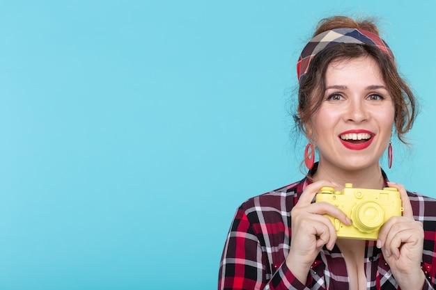 Portret całkiem młoda pozytywna kobieta w koszuli w kratę, trzymając żółty filmowy rocznika aparat pozowanie na niebieskiej ścianie. miłośnicy koncepcji fotografii i strzelectwa. przestrzeń promocyjna