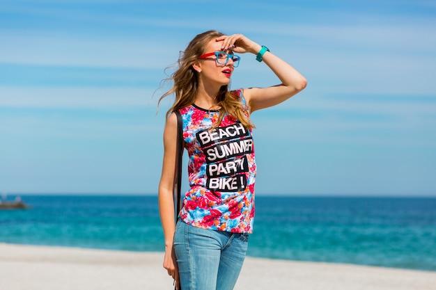 Portret całkiem młoda zmysłowa kobieta z pięknymi blond włosami i okularami przeciwsłonecznymi, pozowanie na rajskiej tropikalnej plaży