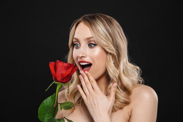 Portret całkiem młoda zszokowana blond kobieta z jasny makijaż czerwone usta pozowanie na białym tle gospodarstwa kwiat róży.