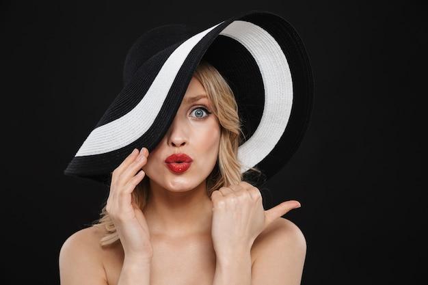 Portret całkiem młoda zszokowana blondynka z jasnym makijażem czerwone usta pozowanie na białym tle na sobie kapelusz.