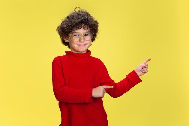Portret całkiem młodego kręconego chłopca w czerwonym ubraniu na żółtej ścianie studia