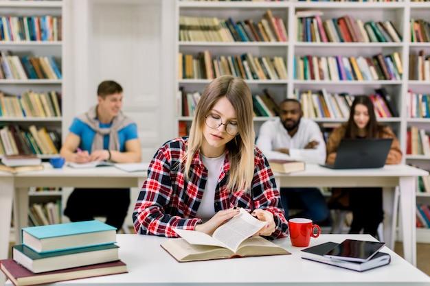 Portret całkiem młodej dziewczyny studentów studiujących w bibliotece kolegium, siedzącej przy stole i czytającej podręcznik.