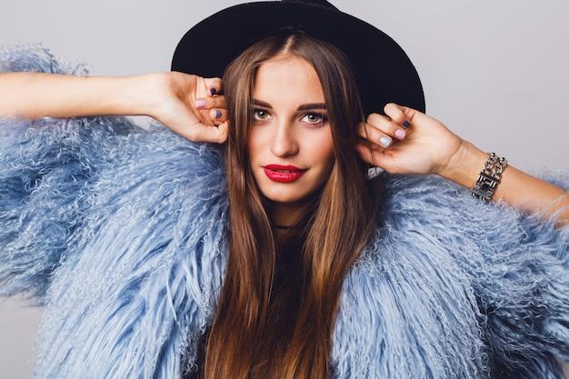 Portret całkiem młody model w stylowy zimowy puszysty płaszcz i czarny kapelusz pozowanie