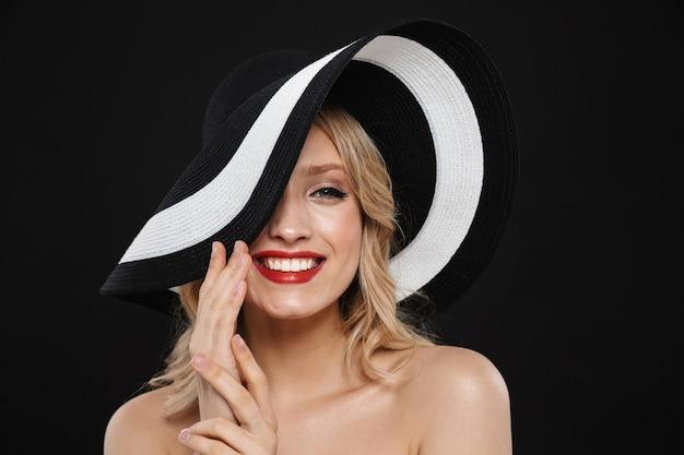 Portret całkiem młody szczęśliwy wesoły blond kobieta z jasny makijaż czerwone usta pozowanie na białym tle sobie kapelusz.