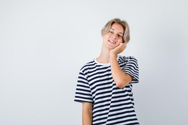 Portret całkiem nastoletniego chłopca opierając się policzkiem na dłoni w pasiastym t-shircie i patrząc na wesoły widok z przodu