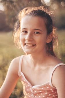 Portret całkiem piękna, młoda dziewczyna w wieczornym słońcu w przyrodzie. dziewczyna korzystających z letniej i słonecznej pogody na łące.