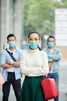 Portret całkiem poważne młoda kobieta azji w żółte okulary stojąc na ulicy miasta i patrząc na kamery