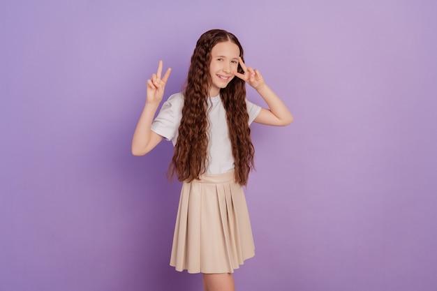 Portret całkiem przyjaznej małej dziewczynki pokazuje dwa znaki v pozujące na fioletowym tle