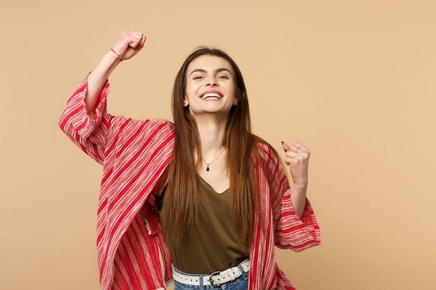 Portret całkiem radosna młoda kobieta w ubraniach casual, zaciskając pięści jak zwycięzca na białym tle na tle pastelowej beżowej ściany w studio. ludzie szczere emocje, koncepcja stylu życia. makieta miejsca na kopię.
