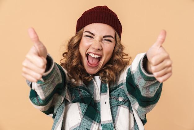 Portret całkiem radosnej kobiety w czapce z dzianiny, śmiejącej się i gestykulującej kciuki w górę, odizolowanej na beżowej ścianie