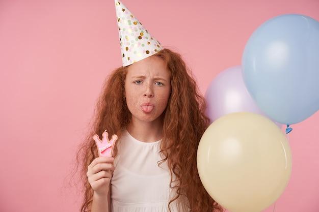 Portret całkiem rudowłosej kobiety dziecko pozuje na różowym tle studia z balonami powietrznymi, marszczy brwi do kamery i pokazuje język, ma na sobie białą sukienkę i czapkę urodzinową