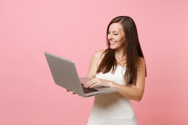 Portret całkiem szczęśliwej kobiety w białej sukni, pracującej na komputerze typu laptop