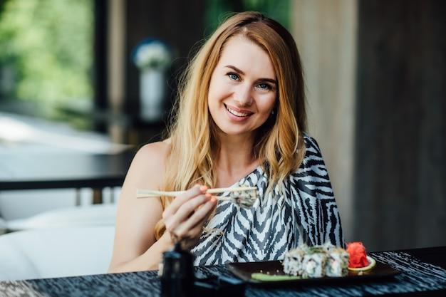Portret całkiem udanej blondynki siedzi w kawiarni na letnim tarasie z zestawem rolek sushi
