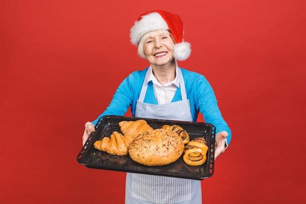 Portret całkiem urocza wesoła kobieta w wieku ze zmarszczkami, pokazując gestykuluje słodkie domowe wyroby piekarnicze