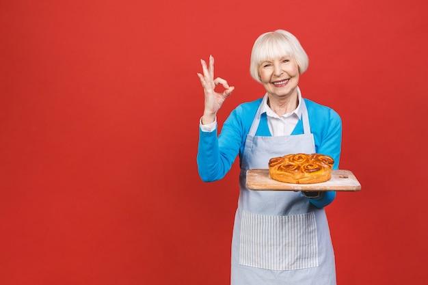 Portret całkiem urocze wesoły starszy kobieta w wieku ze zmarszczkami, pokazując gestykuluje słodkie domowe ciasto