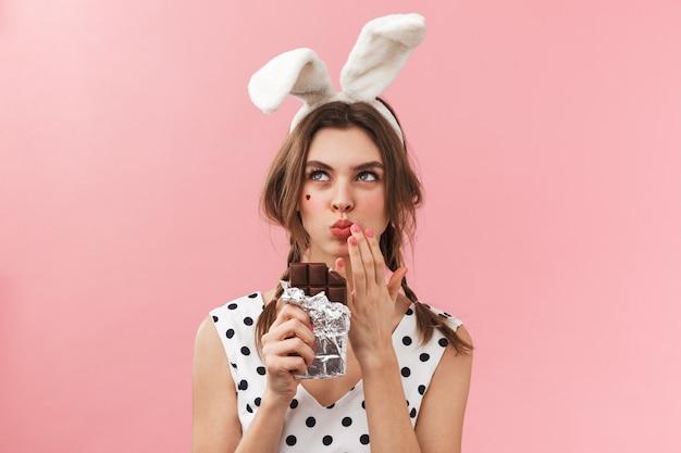 Portret całkiem uroczej dziewczyny sobie uszy królika stojących na białym tle, jedzenie czekolady