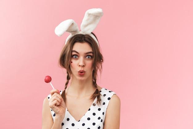 Portret całkiem uroczej dziewczyny sobie uszy królika stojących na białym tle, krzywiąc się, trzymając lizaka
