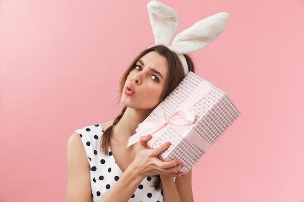 Portret całkiem uroczej dziewczyny sobie uszy królika stojących na białym tle, trzymając pudełko