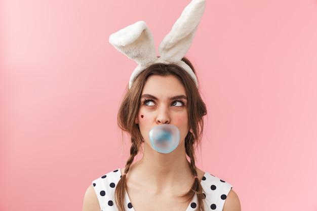 Portret całkiem uroczej dziewczyny sobie uszy królika stojących na białym tle, żucie gumy balonowej