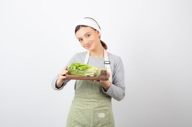 Portret całkiem uroczej kobiety trzymającej drewnianą deskę ze świeżą sałatą