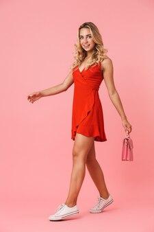 Portret całkiem uśmiechający się ładny młoda blondynka pozuje na białym tle nad różową ścianą spaceru trzymając torbę w rękach.