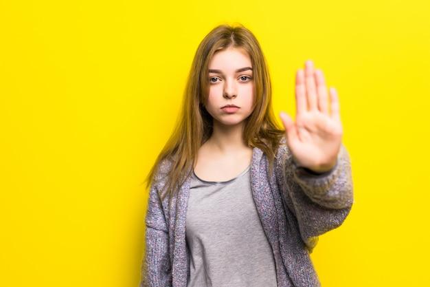 Portret całkiem uśmiechnięta kobieta na białym tle na żółtej ścianie. dziewczyna robi gest stopu ręką