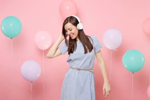 Portret całkiem uśmiechnięta młoda kobieta z zamkniętymi oczami ze słuchawkami w niebieskiej sukience słuchania muzyki na różowym tle z kolorowych balonów. urodziny wakacje party ludzie szczere emocje.