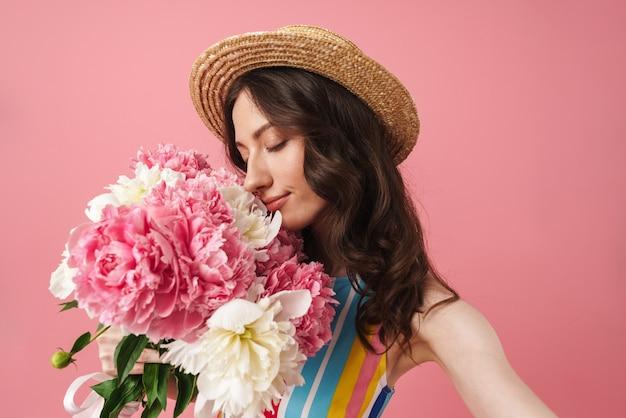 Portret całkiem uśmiechniętej słodkiej kobiety pozującej na białym tle nad różową ścianą pachną kwiatami wziąć selfie przez aparat
