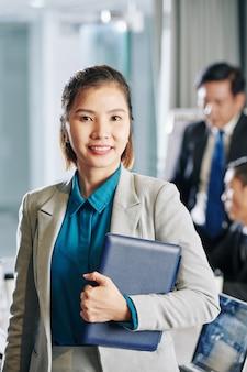 Portret całkiem uśmiechnięty młody przedsiębiorca kobiece pozowanie z komputera typu tablet w sali konferencyjnej